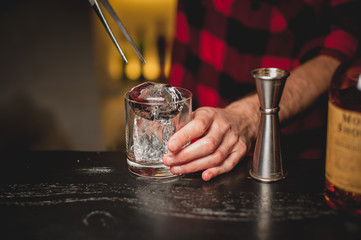 Barman pouring ice in glass.Bartender preparing cocktail drink.