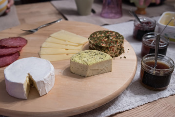Cheese platter with different cheese with jam on table