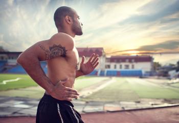 Athlete training. Muscular athlete of the treadmill at the stadium