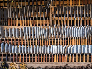 Many kind of knifes on wooden shelf