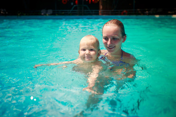 closeup mother small daughter swim smile in azure water of pool