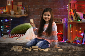 Pretty little girl playing with wooden meccano in Christmas decorated room