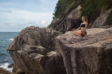 meditation.photo of the girl who is sitting in the lotus position on the rocks at the water