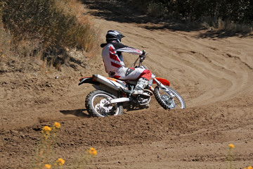 MX rider on a motorcycle rides cornering along the sandy furrow motocross track