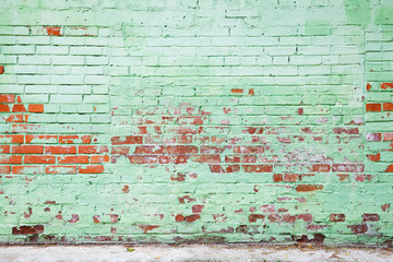 Old brick wall with damaged layer of green paint