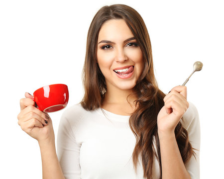 Happy beautiful woman with cup of coffee and spoon isolated on white background