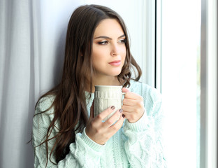 Pretty woman sitting on the window board with cup of coffee