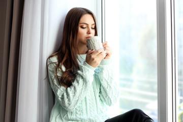 Woman drinking coffee near window in the room
