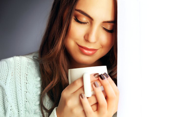 Portrait of pretty young woman with cup of coffee, close up