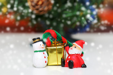 Santa Claus with  snow man and gold gift box on snow