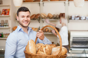 Attractive young guy is purchasing fresh bread