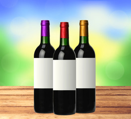 bottles of red wine on wooden table over bright nature backgroun
