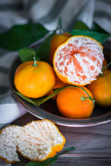 Tangerines with leaves on rustic wooden background