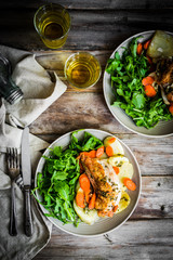 Chicken with potatoes and arugula salad on rustic background
