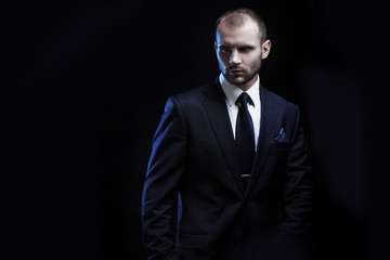 serious man in a business suit, dark background, backlight blue tones