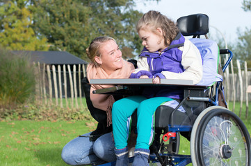 Disabled child in a wheelchair relaxing outside with help from a care assistant / Disabled child in a wheelchair relaxing outside together with a carer