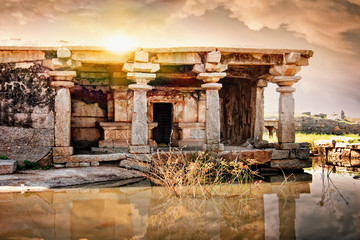Fototapete - Ancient ruins of Vijayanagara Empire in Hampi at sunset sky, Karnataka, India.