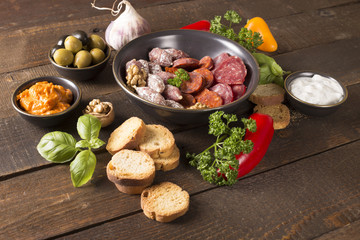 appetizer with sausages,pesto,olive and nuts