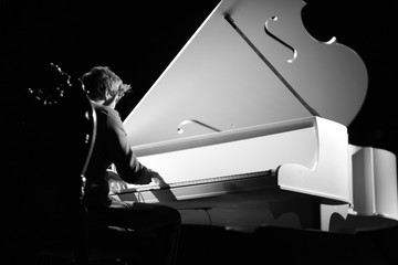 Young musician playing the grand piano