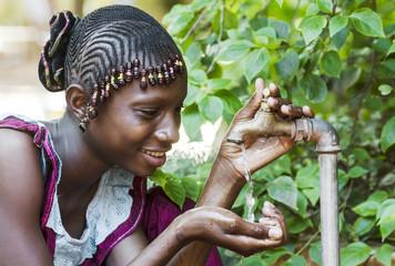 Happy African Schoolgirl Enjoying Clean Water from a Tap in Bamako, Mali