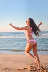 Pretty girl in pink bikini dancing on sunny seaside beach