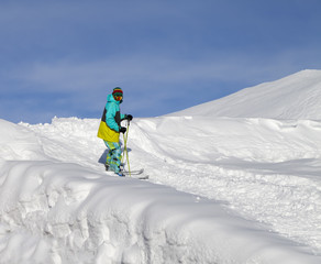 Skier on off-piste slope in sun day