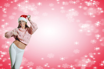 Beautiful young woman in Santa hat dancing on snowflakes background