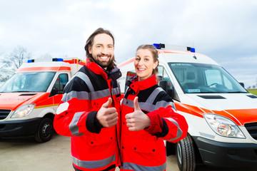 Notarzt und Sanitäter stehen vor einem Rettungswagen