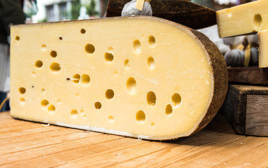 Quarter of Emmental cheese head on the market place. Close-up
