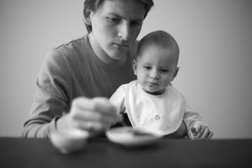 Loving dad feeding his little son