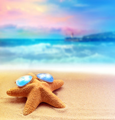 Starfish in sunglasses on a summer beach