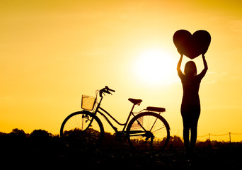 Silhouette of a woman with a bicycle and holding big hearts