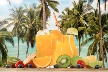 Fresh Fruits on the beach at a deck in front of an tropical islands. Assorted tropical fruits, orange, kiwi, lime, strawberries and blueberries and orange fresh juice.