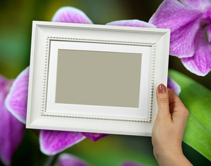 Wooden frame in woman hands on the background closeup of orchid flower