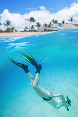 Woman snorkeling underwater at a tropical island resort