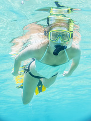 Underwater portrait of a woman snorkeling in clear tropical sea