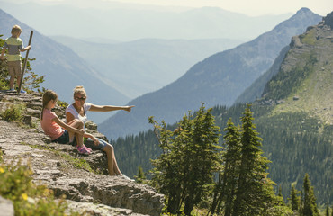 A family sitting together on a rocky ledge looking at a gorgeous view while visiting Glacier National Park in the Rocky Mountains