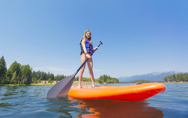 Cute Child paddling on a Stand Up Paddle board on a beautiful, peaceful Mountain lake. Low angle view