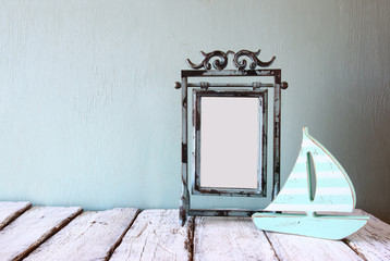image of old victorian steel blue blank frame and wooden sailing boat on wooden table