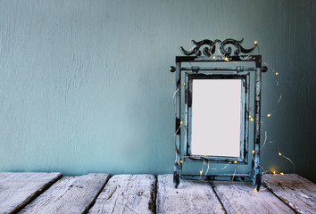 low key image of old victorian steel blue blank frame with fairy garland lights. retro filtered image