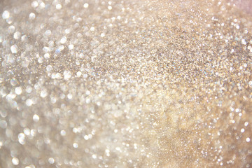 glitter vintage lights background. gold, silver, and white. de-focused.