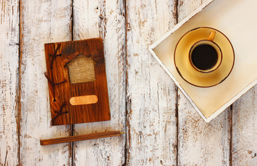 top view image of cup of coffee on wooden white tray and notebook, over wooden table