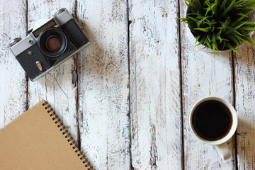 top view image of blank notebook, cup of coffee and old camera