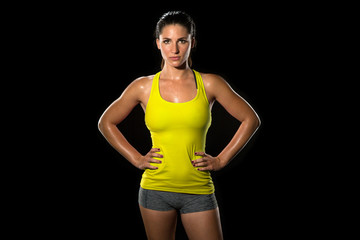 Attractive fit thin slim toned female body athlete isolated on black standing confidently pose powerful woman