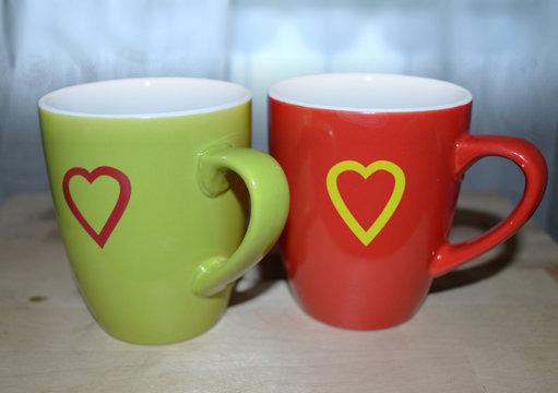 Зеленая и красная чашки с нарисованными сердечками