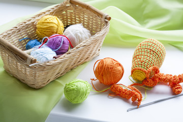 Making of handmade colorful crochet toys sweets (key ring) with skein on wooden table. Selective focus.