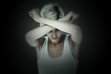 Composite image of upset woman holding her arms in front of her