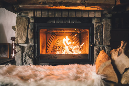 Warm cozy fireplace with real wood burning in it. Cozy winter concept. Christmas and travel background with space for your text