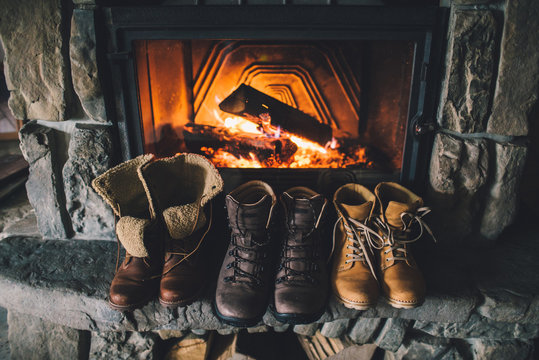 Winter boots in front of a fireplace. Family vintage folk boots drying near the fireside. Warm cozy fireplace in the authentic chalet. Hipster shoes getting warm near the burning fire in a cabin