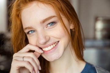 Smiling redhead woman looking at camera